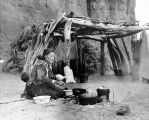 Hosteen Cly's Grand-daughter preparing a meal over her small out-door fire.