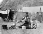 A Navajo mother, Hosteen Cly's Grand-daugher, prepares fried bread while her small son sits...