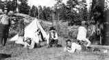 [Camping near Lake Mary. Seven people in front of tent; two standing on their heads.]