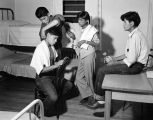 [Boys near bunkbeds dormitory room-One boy is giving another a haircut].